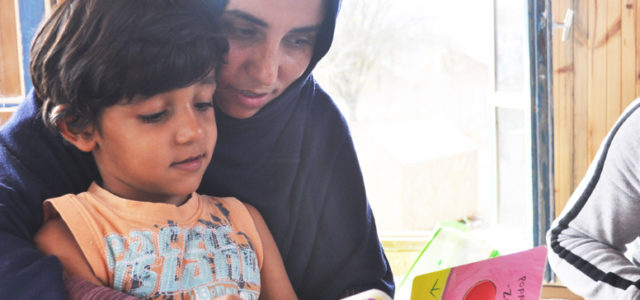 Afghan refugee Habiba reading to her son