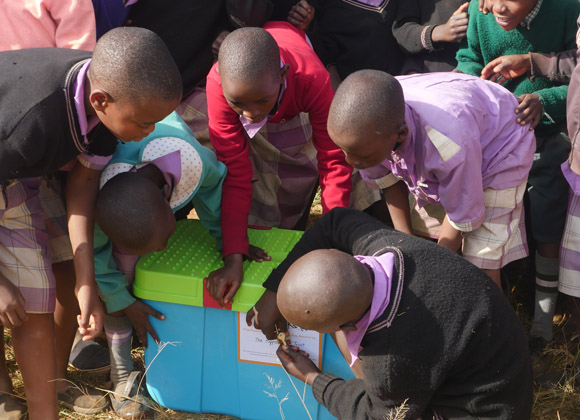 Children greet their new Pioneer Book Box with excitement in Kenya